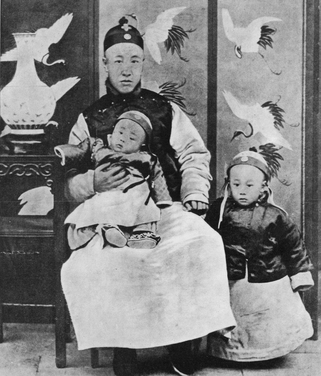 1909: Príncipe Chun, regente y controlador de la Nación, con su hijo menor de rodillas y Puyi (1906-1967) Emperador de China, a su lado.