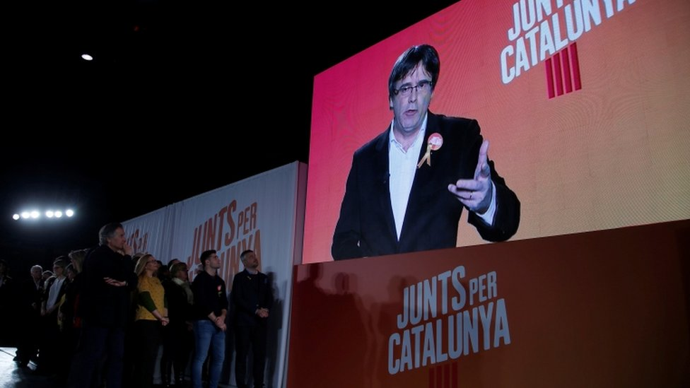 """Ousted Catalan leader Carles Puigdemont appears on a screen during an event of his political platform """"Junts per Catalunya"""" to mark the official start of the electoral campaign"""