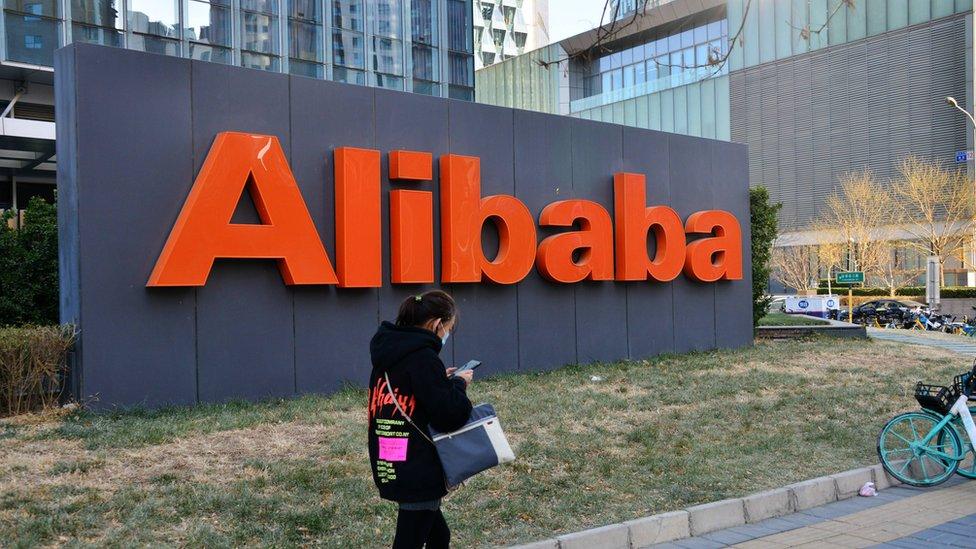 Una mujer frente a un anuncio de Alibaba