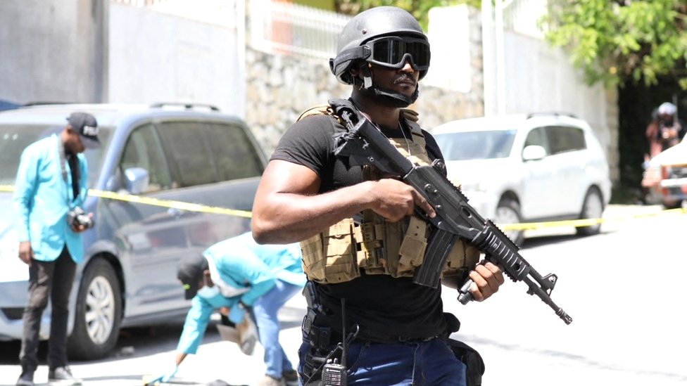 Members of the Haitian police and forensics look for evidence outside of the presidential residence
