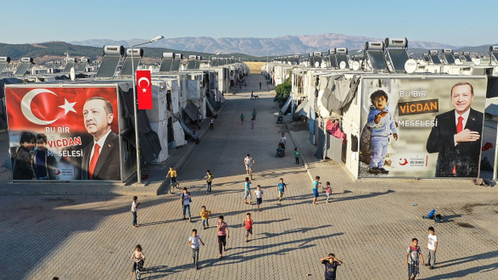 Syrian refugee children play in front of a poster of Turkey's president at a refugee camp in Kahramanmaras, Turkey