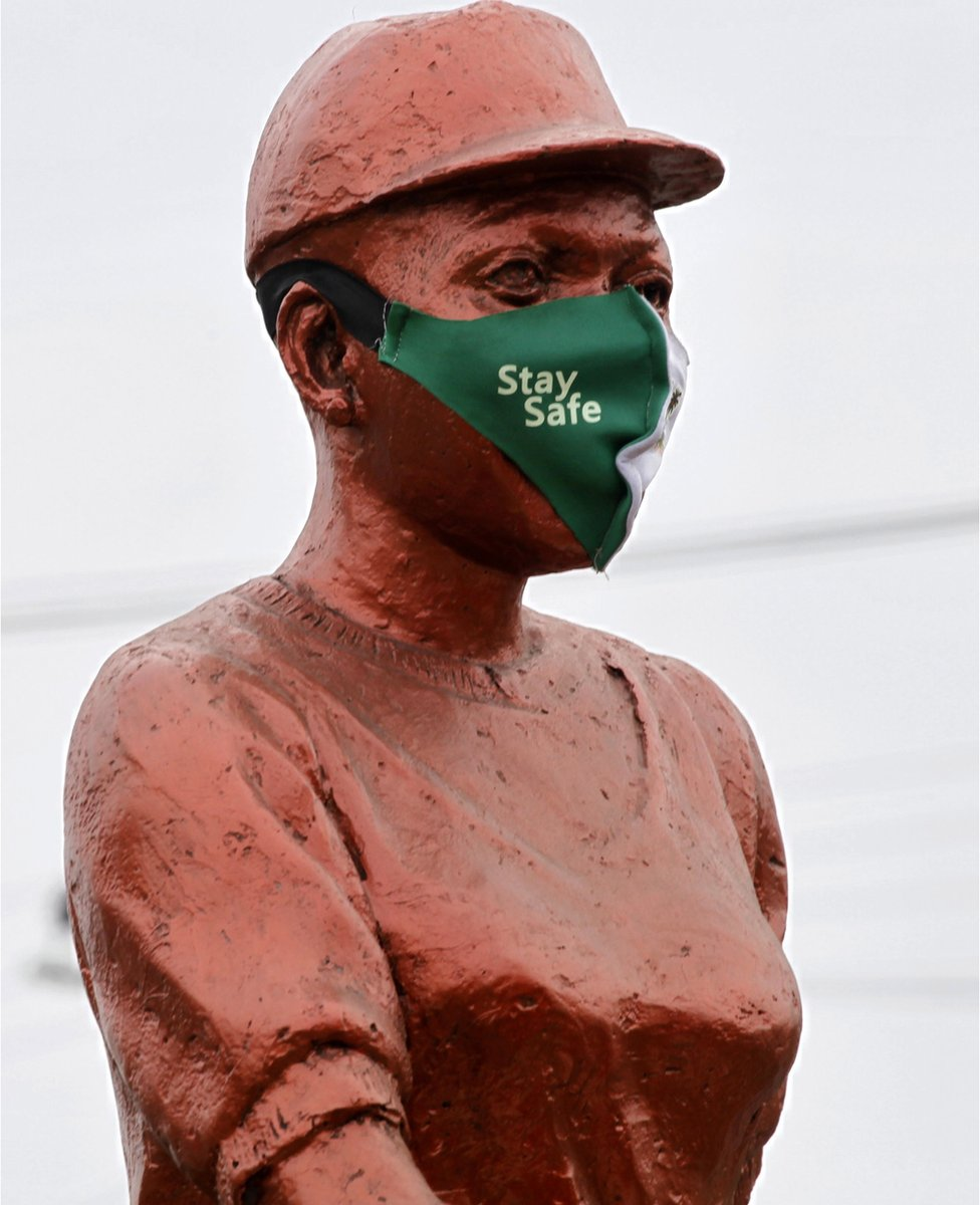 """A bronze-coloured statue is fitted with a mask with a caption that reads """"stay safe""""."""