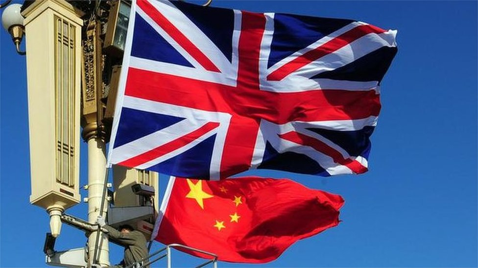 Union Jack flag is hoisted next to the flag of the Peoples Republic of China in front of Tiananmen Gate