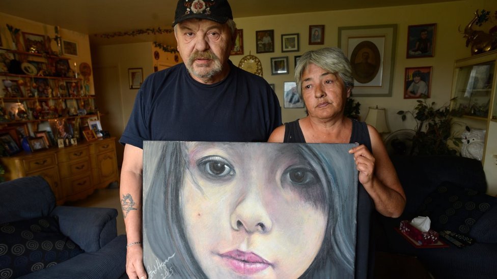 oe and Thelma Favel and a framed collage tribute to their niece, Tina Fontaine, who was murdered and her body dumped in the Red River