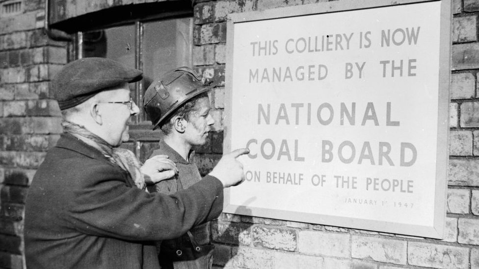Two miners reading a sign at a colliery informing them of nationalisation