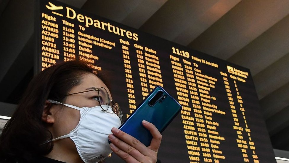 A passenger wearing a respiratory mask speaks on her smartphone by the departures board.