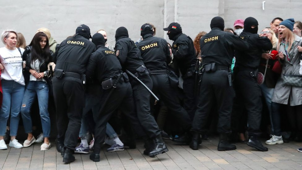 Riot police grab people in order to detain them, from a crowd of women on 8 September