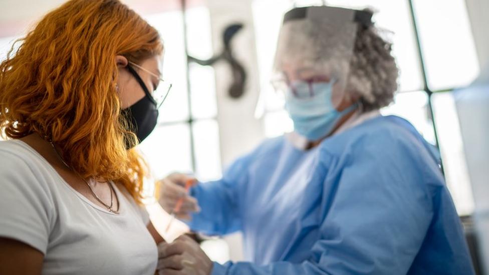 Mulher é vacinada por profissional da saúde