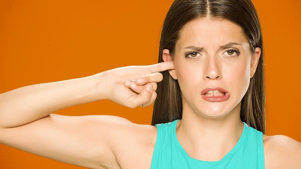 Mujer mintiéndose el dedo en el oído