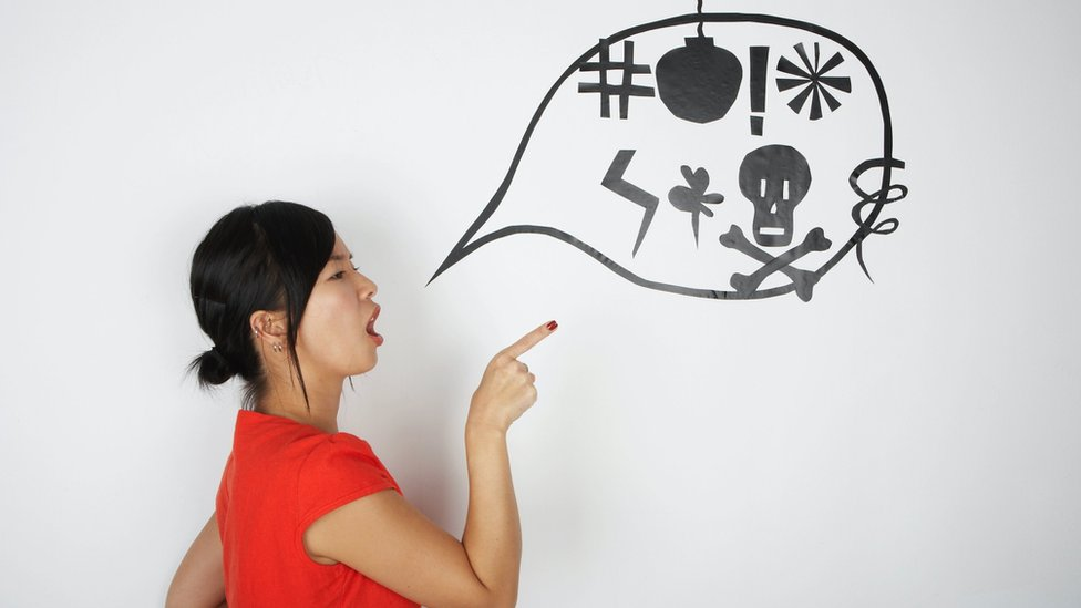Concept image: an angry young woman points her finger and opens her mouth, in front of it there's a bubble speech with symbols meaning swear words