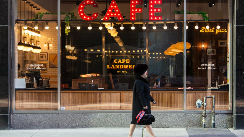 A woman in a mask walks through downtown Toronto, 7 October, 2020