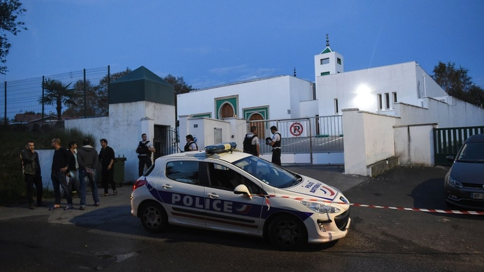 French police officers and people stand in front of the mosque of Bayonne on 28 October 2019, after two people were injured in a shooting