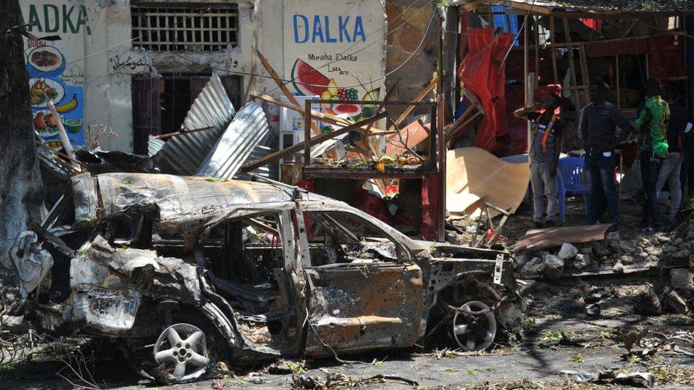 Los escombros de un auto destrozado por una bomba frente a tiendas de comercio en la capital somalí de Mogadiscio