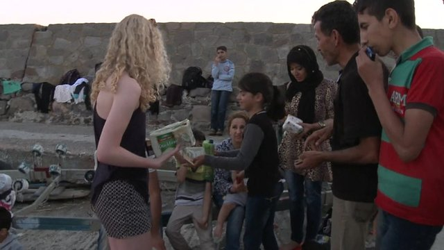 A Danish tourist hands out biscuits to a group of refugees