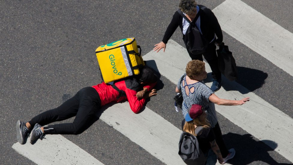 A Glovo's delivery boy lies over the 9 de Julio avenue as pedestrians try to help after a car crashed him in the intersection with the Av. de Mayo Avenue, Buenos Aires, Argentina,Sunday, November.25,2018.