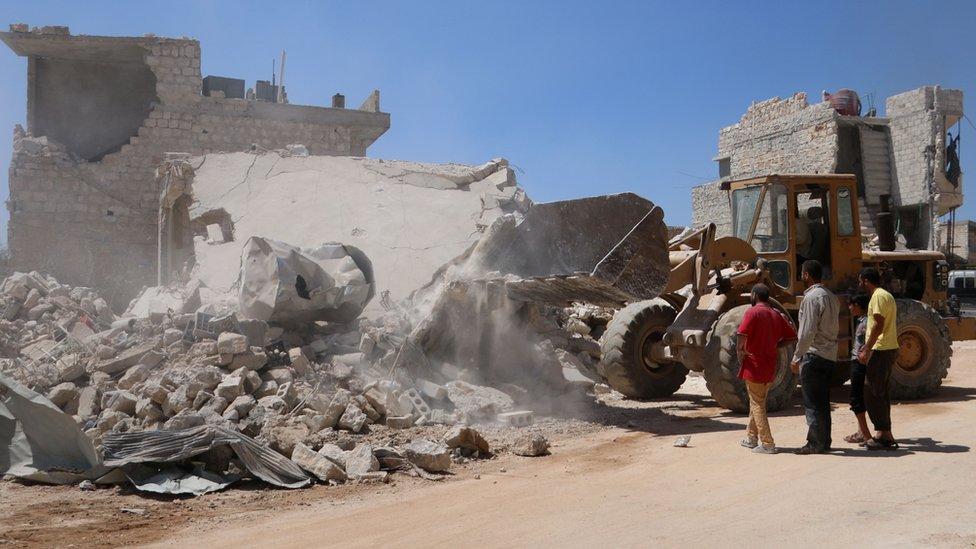 Buldožer čisti ruševine nakon vladinog bombardovanja pobunjenika koji su držali grad Urum al-Kubra
