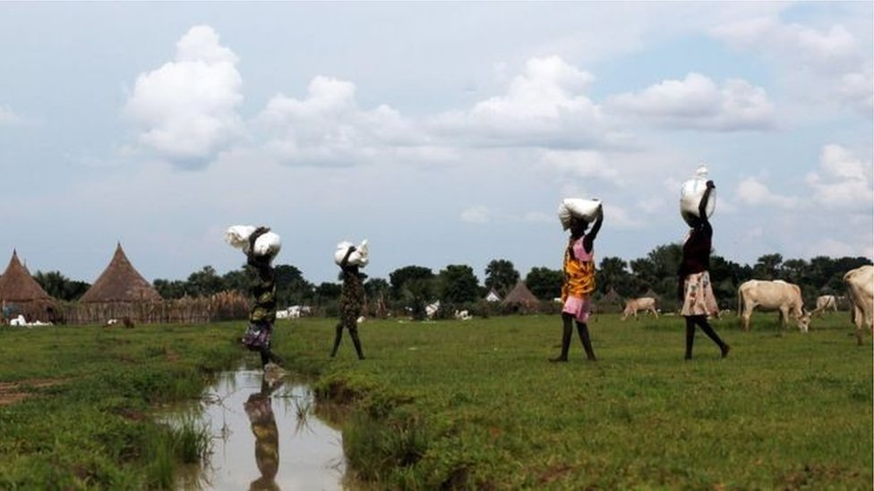 نساء يمشين معاً ويحملن مساعدات غذائية على رؤوسهن