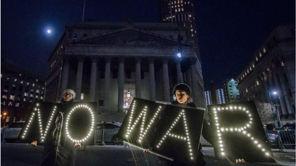 Manifestantes con luces que dicen No War