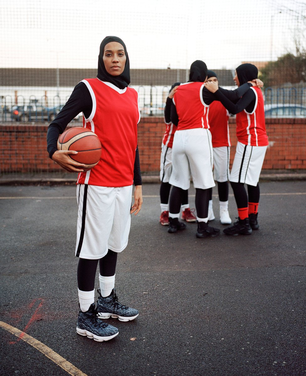 Portrait of Asma standing on a basketball court with her teammates behind her
