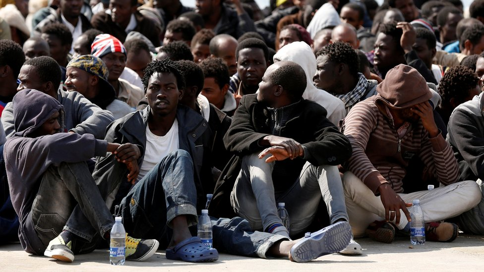Migrants rest after disembarking from the Italian Navy vessel Grecale in the Sicilian harbour of Augusta