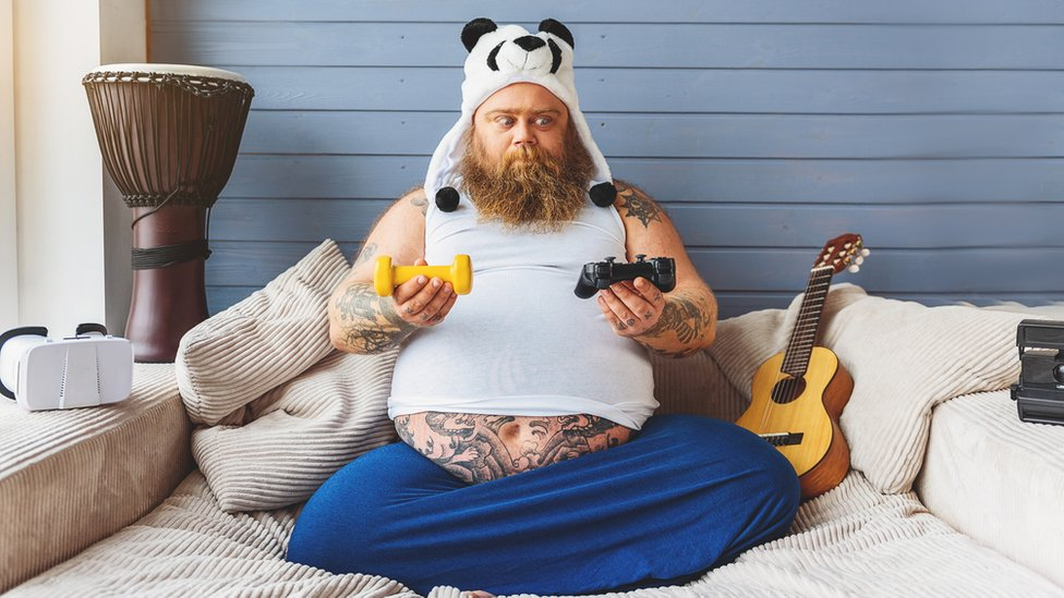 Un hombre preguntándose si deberá hacer ejercicio o jugar videojuegos