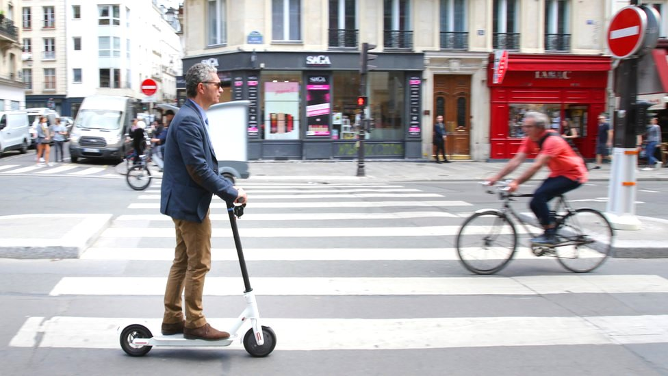 A man rides an electric scooter on the Rue de Rivoli street in Paris, France, 17 June 2019