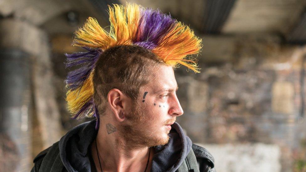 Un hombre con la cara tatuada y el pelo estilo punk y de colores vistosos