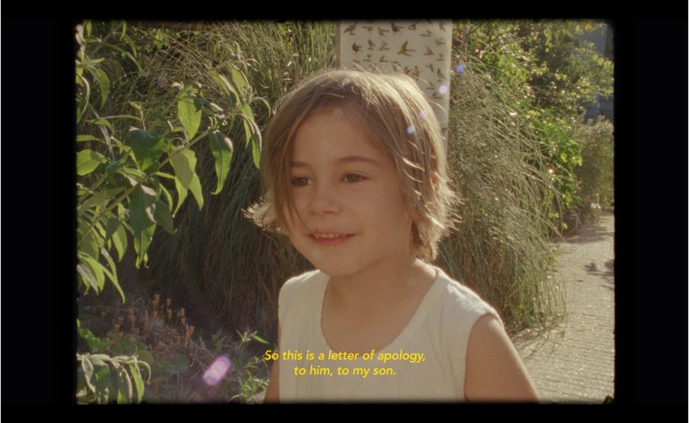 """A film still of a child with subtitles saying """"So this is a letter of apology, to him, to my son"""""""