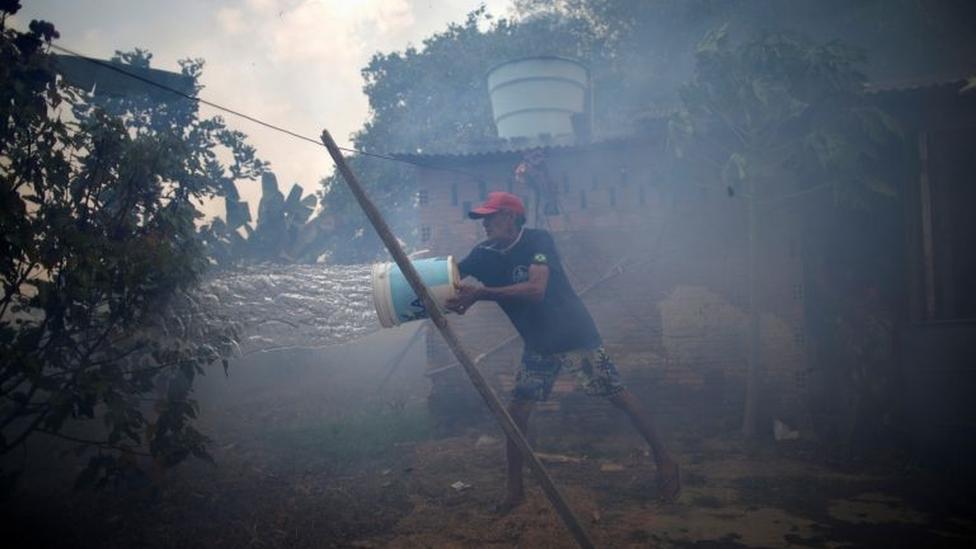 Homem joga balde d'água em área do quintal, coberta por fumaça