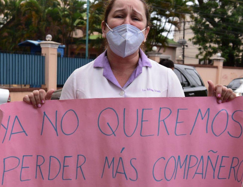 """Una mujer con un cartel que dice: """"Ya no queremos perder más compañeros"""", en Paraguay."""