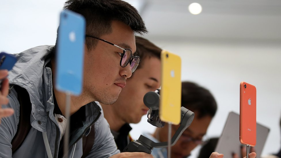 People looking at Apple's iPhone XR.