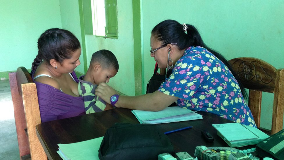 A doctor checks a child on the porch of Maria Torres' home