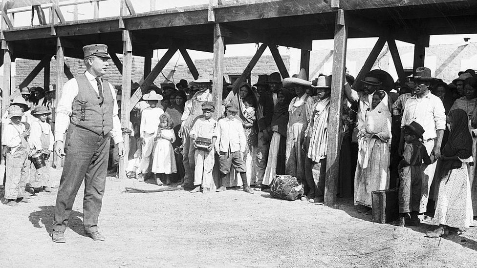 Un funcionario fronterizo estadounidense les habla a un grupo de refugiados mexicanos en el Puente Internacional de El Paso, en Texas. Año 1916.