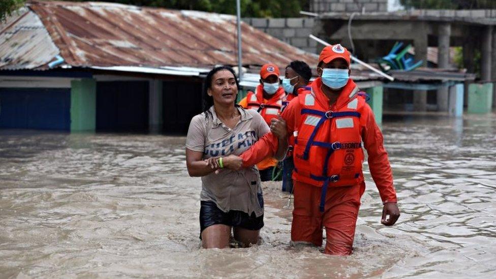 La defensa civil de República Dominicana rescata a una mujer tras las inundaciones causadas por la tormenta Laura.
