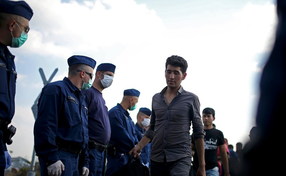 Migrants are escorted by Hungarian police officers as they wait to board a bus at a migrant collection point near the Serbian Hungarian border in Roszke, Hungary September 13, 2015.