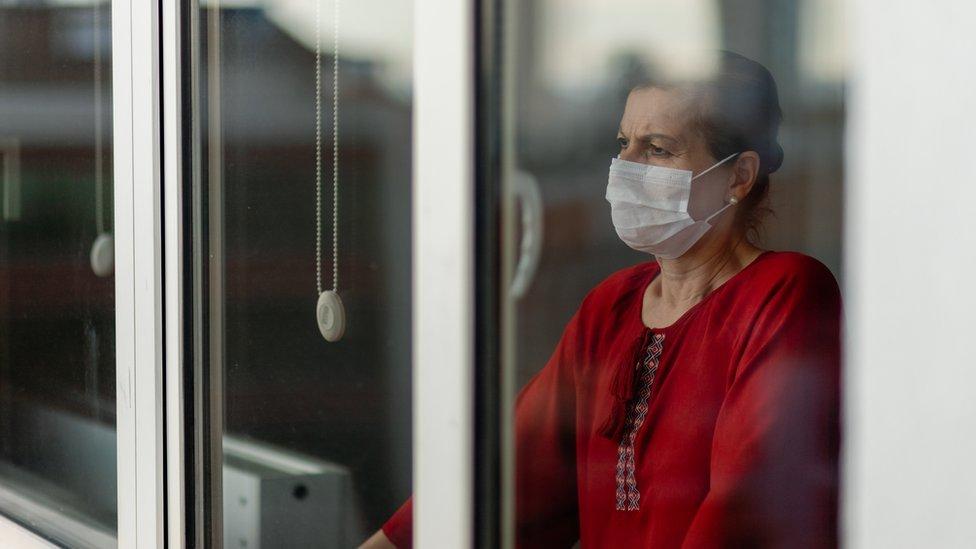 Una mujer con mascarilla parada detrás de en una ventana.