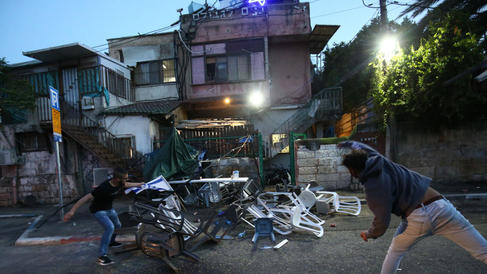 Two men throwing chairs at a house flying the Israeli flag in Sheikh Jarrah