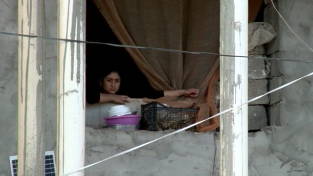 Young Iraqi women looking out of window in a refugee camp
