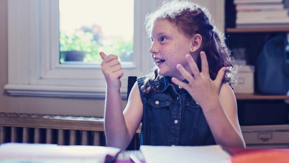 Un niña cuenta con los dedos de la mano.