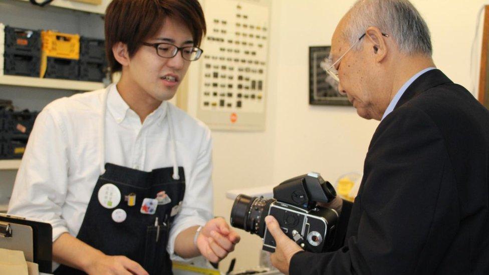 Un cliente de la tienda de Inada examina una vieja cámara.