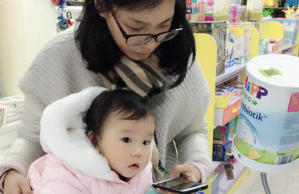 Mother uses phone to verify authenticity of baby formula