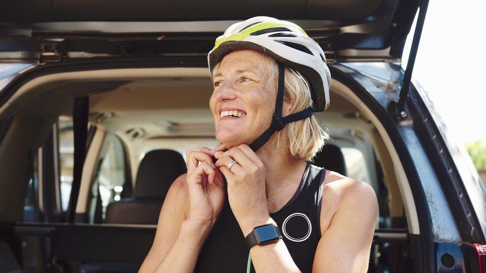 Una mujer se pone un casco de bicicleta.