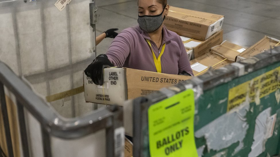Postal worker unloads thousands of boxes filled with votes in Oregon