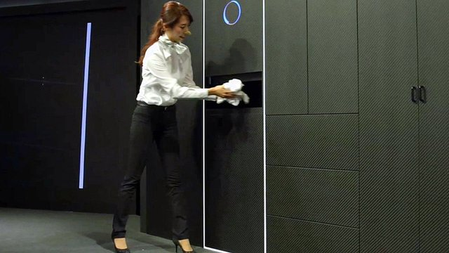 A woman placing laundry into Laundroid