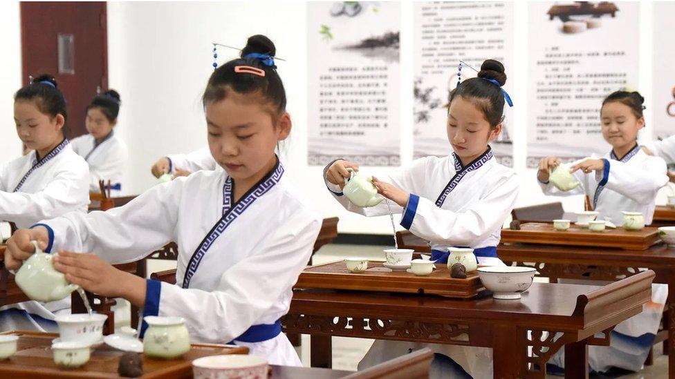 Niñas asiáticas practican el ritual del té