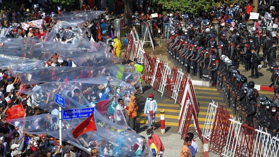 Algunos manifestantes protestaron bajo plásticos para protegerse de los cañones de agua.