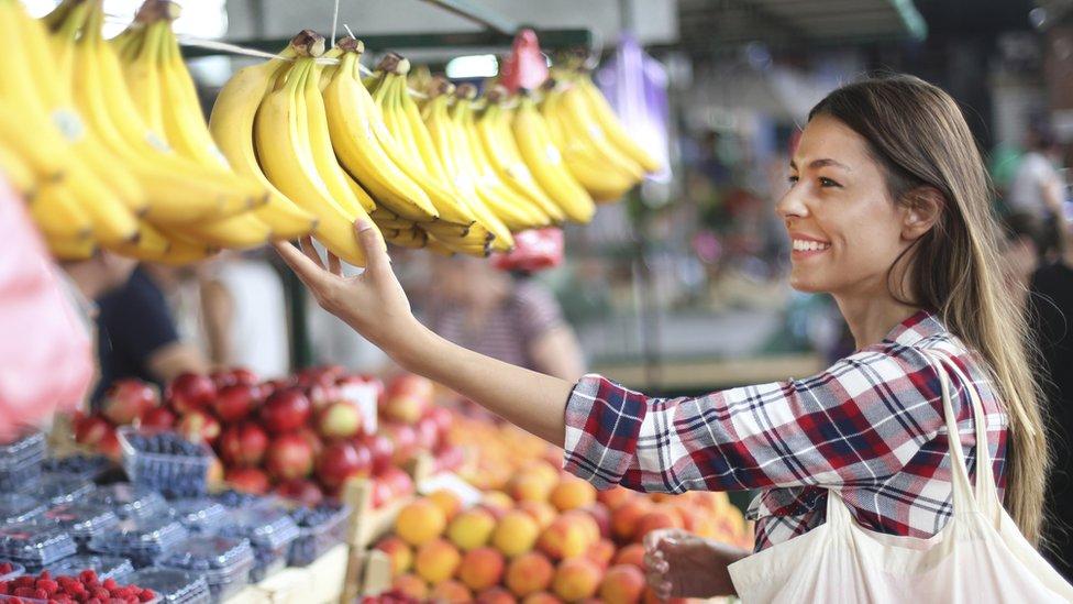 Mujer comprando bananas en un mercado.