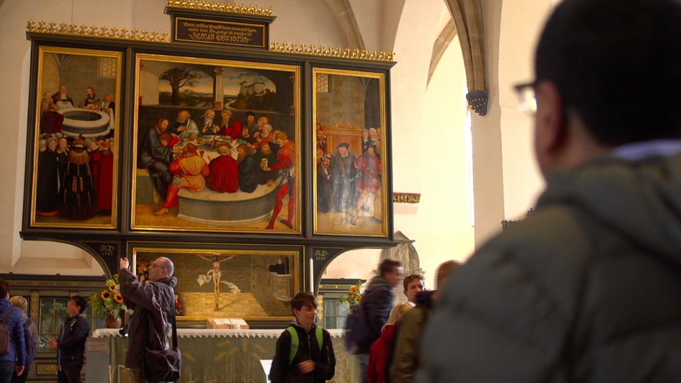 Martin Bashir stands looking at altarpiece picturing the Last Supper