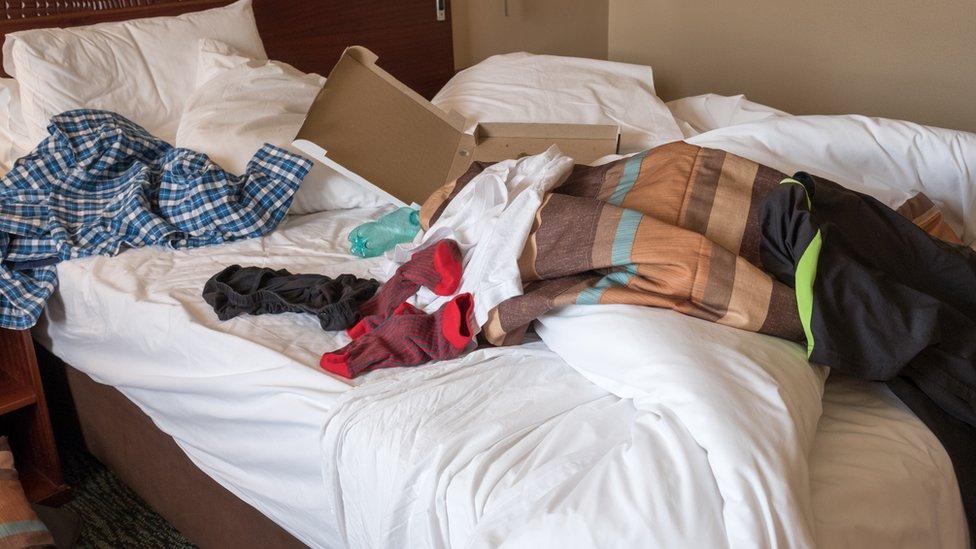 Una cama desarreglada con ropa y una caja de cartón encima.