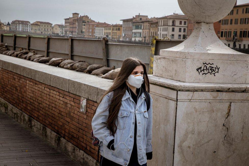 Mujer con mascarilla en Pisa, Italia.